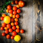 Colorful tomatoes on rustic background